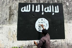 A resident painting over an ISIS flag in Solo, Central Java.