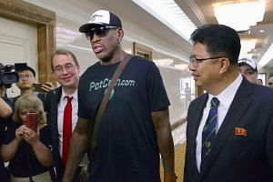 Former US basketball star Dennis Rodman (centre) arriving at Pyongyang's international airport, North Korea on June 13, 2017.