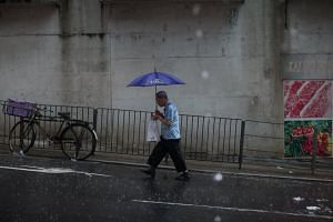 A man holds an umbrella during a torrential rain brought by tropical storm Merbok in Hong Kong, China on June 13, 2017.