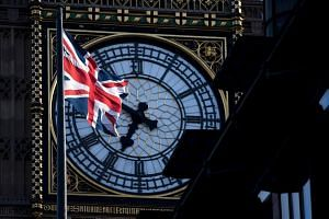 A Union flag flies in the wind in front of the clock face of Elizabeth Tower, in Westminster, central London on April 18, 2017.