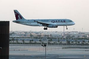 A Qatar Airways plane lands at the Hamad International Airport in the Qatari capital Doha on June 12, 2017.