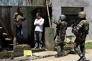 Government soldiers searching a man during a security inspection in Marawi. A coalition of local insurgent groups loyal to ISIS began their assault on the city on May 23, announcing their intent to create a caliphate. Since then, more than 300 people