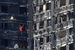 Members of the emergency services work inside burnt out remains of the Grenfell apartment tower in North Kensington, London, Britain, on June 18, 2017.