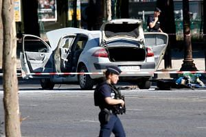 Police secure the area near a burned car at the scene of an incident in which it rammed a gendarmerie van on the Champs-Elysees Avenue in Paris, France on June 19, 2017.