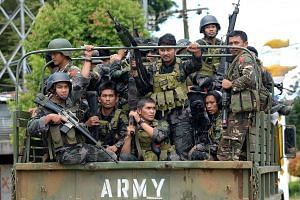 Members of the Philippine police special action force ride in an army truck on their way to the frontline in Marawi on June 19, 2017.