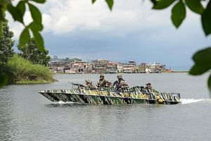 Marawi residents, who fled their homes to avoid the fighting, collecting drinking water in Pantar village, Lanao del Norte, southern Philippines, on Sunday. Philippine Army soldiers on lake patrol near the front line in Marawi, Mindanao, on Monday, a