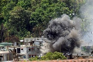 Debris and smoke shroud a building as government forces continue their assault against insurgents who have taken over large parts of Marawi City.