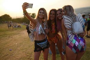 Festival-goers pose for a selfie photograph at the Glastonbury Festival of Music and Performing Arts on Worthy Farm near the village of Pilton in Somerset, South West England. PHOTO: AFP