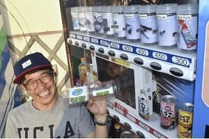 Mr Yuichi Ikeda holding a container of surfboard wax sold at his vending machine in Miyazaki Prefecture. It is literally a lifesaver for surfers who have forgotten important items.