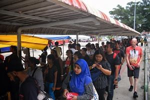 People queueing at the Queen Street bus terminal to take buses to Johor Baru at around 5.15pm yesterday. Coach operators Aeroline and KKKL, which offer services between Singapore and Malaysia, said their buses were fully booked for the day.