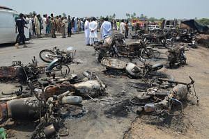 People gather behind burnt motorcycles and vehicles at the scene of an oil tanker accident on the outskirts of Bahawalpur, Pakistan, on June 25 2017.