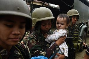 Philippine army troops with a rescued child in war-torn Marawi yesterday. Muslim religious leaders entered the conflict zone yesterday and negotiated with militants to release some civilian hostages.