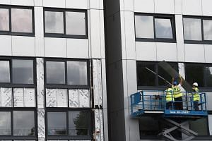 Workers removing cladding from the Whitebeam Court tower block in Salford, north west England on June 26, 2017.