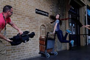 A woman poses for a photograph with the Harry Potter trolley at King's Cross Station, in London.