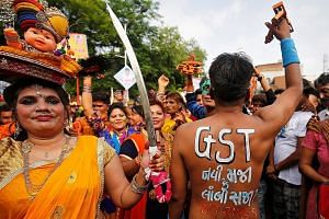 A Hindu devotee at the annual Rath Yatra, or chariot procession, in Ahmedabad, India, on Sunday, with a message on his back asking if the new tax is a boon or burden. The GST will be rolled out next month.