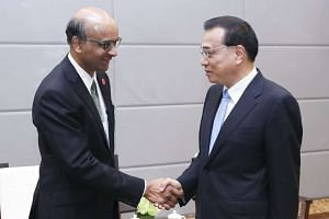 Deputy Prime Minister Tharman Shanmugaratnam (left) called on Chinese Premier Li Keqiang yesterday in Dalian, on the sidelines of the World Economic Forum's Summer Davos meeting.