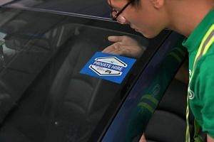 A Grab employee pasting a private-hire car decal.