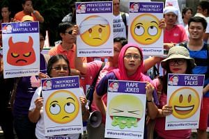 Various activists groups hold emoji-riddled placards as they join other protesters in airing their individual concerns marking President Rodrigo Duterte's first year in office during a protest outside the presidential palace in metro Manila, Philippi