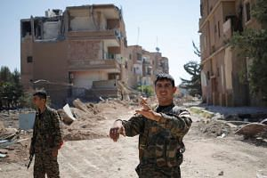 A Kurdish fighter from the People's Protection Units (YPG) gestures in Raqqa, Syria, on June 27, 2017.