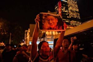 An activist holds a poster of terminally-ill Nobel laureate Liu Xiaobo on the sidelines of a vigil for him in Hong Kong on June 29, 2017.