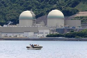 A boat of the Japan Coast Guard patrols in front of the No. 3 reactor (left) at the Takahama nuclear plant in Takahama, Fukui prefecture, some 350 kilometres (215 miles) west of Tokyo on June 6, 2017.