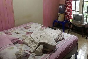 Khasanah (above) was detained on Tuesday in the town of Tungkal Ilir in West Tanjung Jabung regency in Indonesia's Jambi province, after local police raided her room (left) at Hotel Nanber following a tip-off from residents. The maid was seen browsin