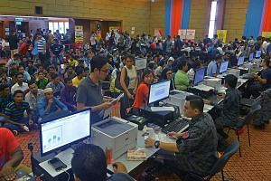 Employers and illegal workers applying for work permits at the Immigration Department headquarters in Putrajaya on Thursday night. The authorities are expected to begin rounding up illegal workers today.