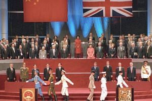 This file photo taken on July 1, 1997, shows a Chinese soldier (second left) holding the national flag prior to its raising as the British military (right) march during the handover ceremony at the Hong Kong Convention and Exhibition Centre.