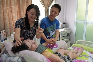 """Ms Grace Koh feeding milk to her bedridden mother with the help of her brother Joshua Koh. The siblings, who both have full-time jobs, also look after their father who needs intensive care after a fall left him with a brain injury. """"At the end of a l"""