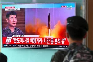 A South Korea soldier watching a news broadcast about a North Korean missile launch, at a railway station in Seoul on July 4, 2017.