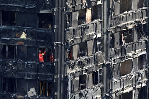Members of the emergency services work inside burnt out remains of the Grenfell apartment tower.