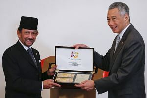 Hassanal Bolkiah (left) and Lee Hsien Loong presenting commemorative fifty-dollar notes from the respective countries during a commemorative note presentation ceremony at the Istana Presidential Palace in Singapore on July 5, 2017.