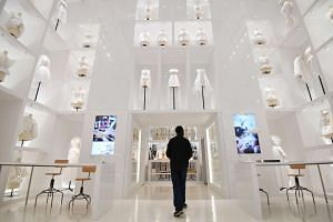 A cleaner inspecting a room prior to the opening of the Dior exhibition that celebrates the 70th anniversary of the Christian Dior fashion house on July 3, 2017 in Paris.