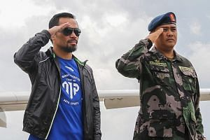 Manny Pacquiao (left) salutes as he arrives in the Philippines to a military guard of honour after losing his welterweight title to Jeff Horn in Brisbane.