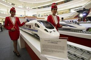 Attendants pose for a photo beside the models of a high speed train during the China High Speed Railway on Fast Track exhibition in Jakarta, on Aug 13, 2015.
