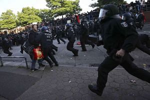 German police officers in full riot gear run after anti-G-20 protesters.