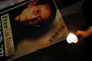 A protester holds a candle next to a portrait of Chinese Nobel rights activist Liu Xiaobo demanding his release in Hong Kong, China on June 29, 2017.