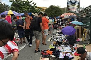 Visitors and stall holders at the last weekend of Singapore's oldest flea market, the Sungei Road Market.