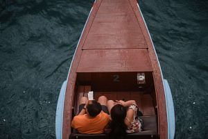 A couple sit next to each other on a gondola at Marina Bay Sands.