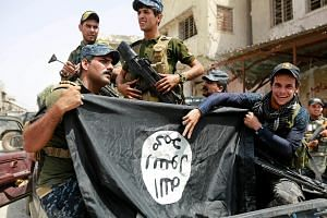Iraqi Federal Police officers holding up an ISIS flag they pulled down in the Old City of Mosul, on July 4, 2017.