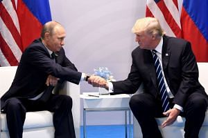 Trump and Putin shake hands during a meeting on the sidelines of the G-20 Summit, July 7, 2017.