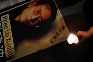 A protester holds a candle next to a portrait of Chinese Nobel rights activist Liu Xiaobo demanding his release, during Chinese President Xi Jinping visiting, ahead of 20th anniversary of the city's handover from British to Chinese rule, in Hong Kong