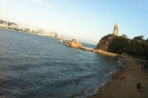 Tourists frolicking in the waters at Xiamen's tourist island Gulangyu, where construction on the main island never stops.