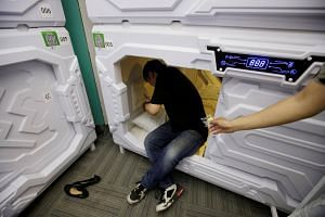 A staff member gives mute earplugs to a customer as he prepares to sleep in a capsule bed unit at Xiangshui Space during lunch break in Beijing's Zhongguancun area, China on July 11, 2017.