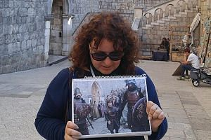 Game Of Thrones guide Tonka Matana with a photo of a scene from the drama showing Tyrion Lannister (Peter Dinklage) inside the old city of Dubrovnik.
