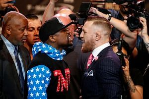 Boxer Floyd Mayweather and mixed martial arts champion Conor McGregor square off.