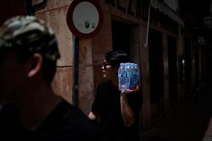 A tourist carries bottles of water during a heatwave in downtown Ronda, Spain, on July 12, 2017.
