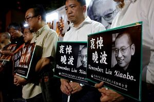 Pro-democracy activists mourn the death of Chinese Nobel Peace laureate Liu Xiaobo, outside China's Liaison Office in Hong Kong, China on July 13, 2017.
