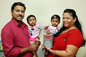 Mr Saravanan, 43, who goes by only one name, and his wife Indra, 37, with their nine-month-old twin daughters Heerthikaa and Hera (right). The couple switched to a more affordable range of formula milk from Australia, which was introduced by FairPric