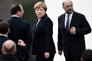 German Chancellor Angela Merkel, flanked by then French president Francois Hollande (left) and then European Parliament president Martin Schulz, at a ceremony last year in Douaumont, France, to mark the centenary of the Battle of Verdun. Mr Schulz's